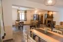 A földszinten egy – rendezvények lebonyolítására is alkalmas - közösségi teret alakítottak ki, és ezzel egy légtérben étkező található. A két helyiséghez teakonyha kapcsolódik. A tetőtérben négy kétágyas szoba kapott helyet, valamennyi saját fürdőszobával és mosdóval rendelkezik.